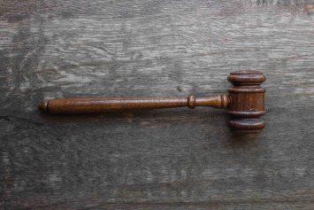 Gerichtshammer aus Holz auf hölzernem Hintergrund